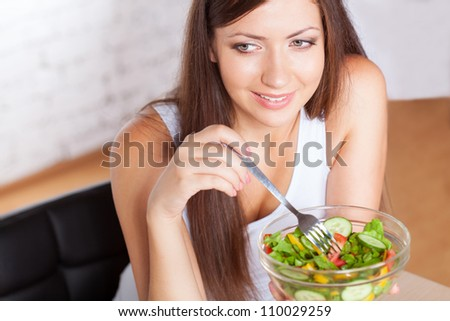 happy brunette woman holding boil with salad