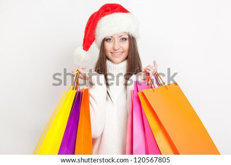 happy  brunette woman in santa hat holding shopping bags