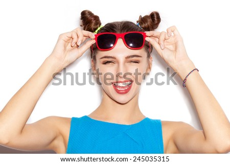 Happy Brunette Woman in sunglasses. Beauty girl with bright makeup hairstyle with horns in a blue dress having fun. On a white background, not isolated - stock photo