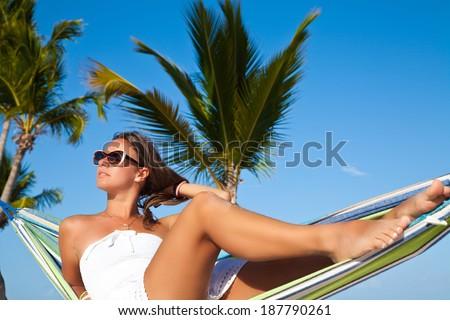 Happy brunette woman relaxing on Caribbean beach in hammock on summer holidays resort.  - stock photo