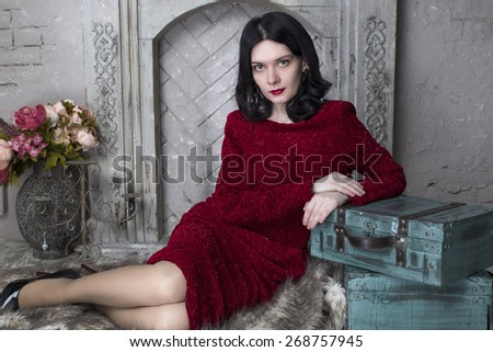 Happy brunette woman sitting near the fireplace - stock photo