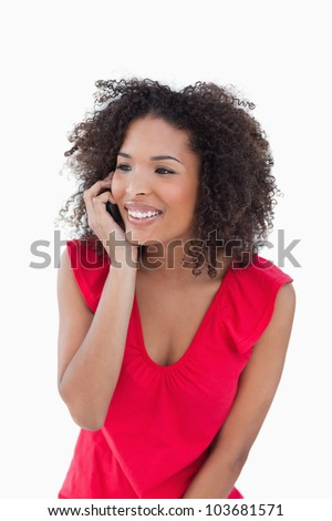 Happy brunette woman using her mobile phone against a white background