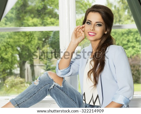 happy brunette woman with long hair and trendy casual modern outfit sitting near bright window on green luxurious garden. Smiling and wearing torn jeans and blue paste jacket  - stock photo