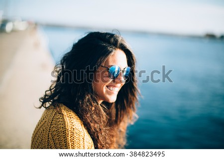 Happy brunette woman with sunglasses smiling while sitting on pier. Summertime - stock photo