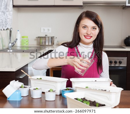 Happy brunette woman working with  seedlings