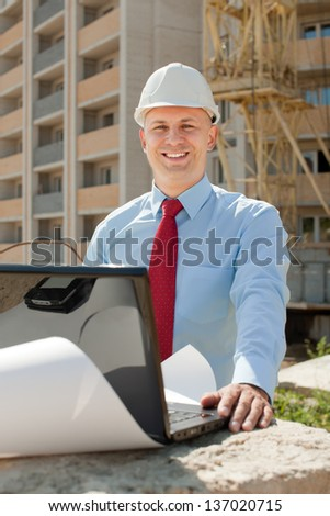 Happy builder in hardhat works on the building site - stock photo
