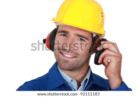 Happy builder wearing ear protection - stock photo
