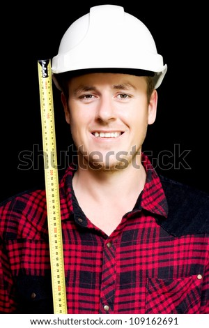 Happy builder with a big smile wearing a safety helmet holding an open tape measure alongside his face, studio portrait on black - stock photo