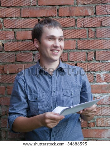 Happy builder with documents against  the brick wall
