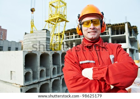 happy builder worker in uniform and safety protective equipment at construction site - stock photo
