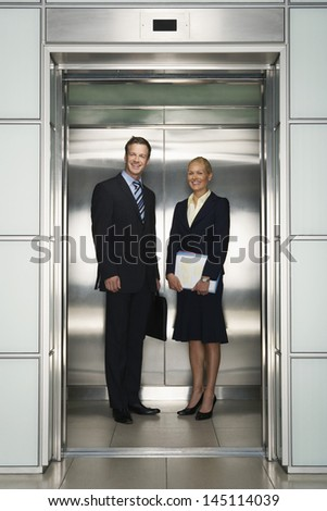 Happy business colleagues looking away while standing in elevator - stock photo