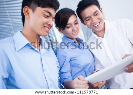 Happy business colleagues looking something on digital tablet - stock photo