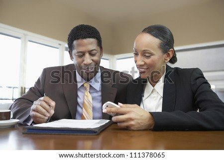 Happy business colleagues reading document at office - stock photo