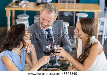 Happy business colleagues toasting wine glass in the restaurant - stock photo