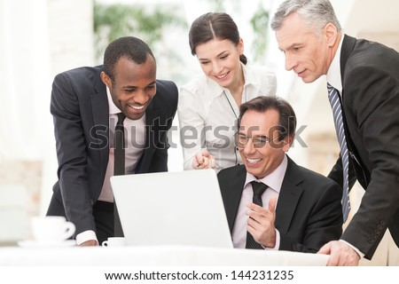 Happy business colleagues working together and discussing project on laptop during meeting - stock photo