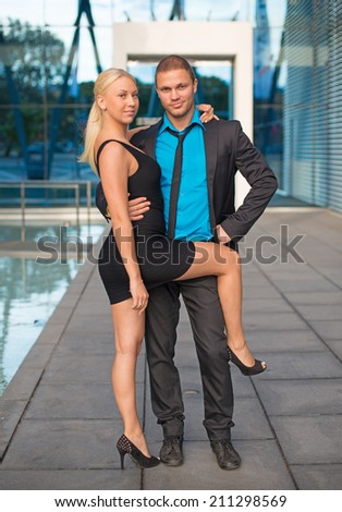 Happy business couple against office building. - stock photo