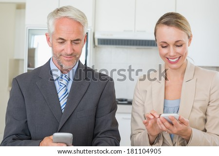 Happy business couple texting before work in morning at home in the kitchen