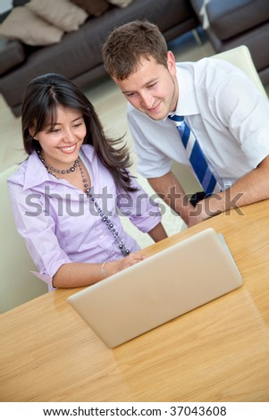 Happy business couple with a computer in an office