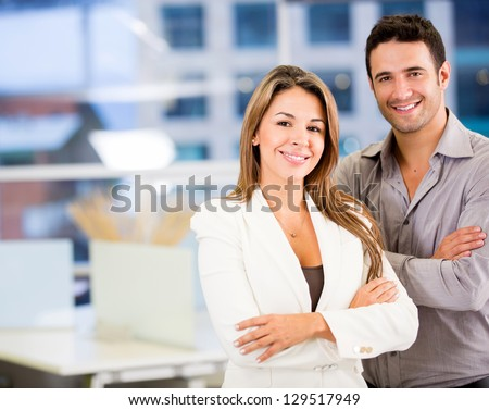 Happy business couple with arms crossed at the office - stock photo