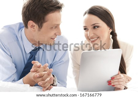 Happy business couple with digital tablet looking at each other in hotel - stock photo