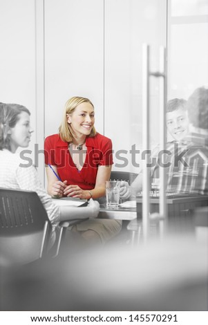 Happy business executives sitting around conference table - stock photo