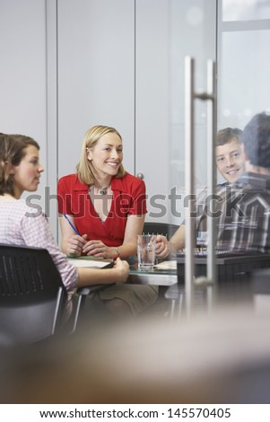 Happy business executives sitting around conference table
