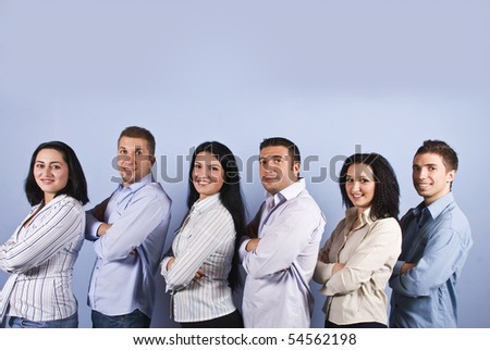 Happy business group with six smiling group standing in a line with arms folded in profile  and looking you on blue background,copy space for text message overhead - stock photo