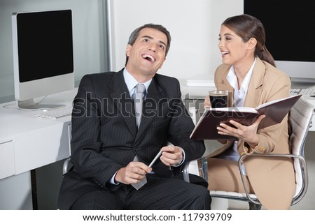 Happy business man and secretary laughing together in the office - stock photo