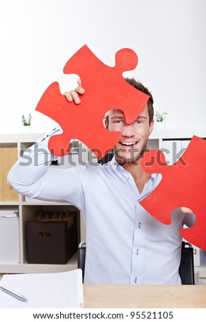 Happy business man cheering with oversized jigsaw puzzle pieces in office - stock photo