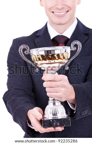 Happy business man handing a trophy over white background - stock photo