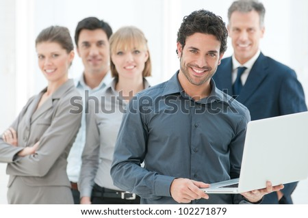 Happy business man holding a modern laptop computer with his team in background - stock photo