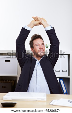 Happy business man in office stretching his back at desk - stock photo