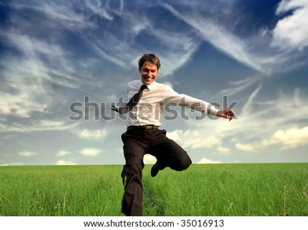 happy business man jumping in the grass - stock photo