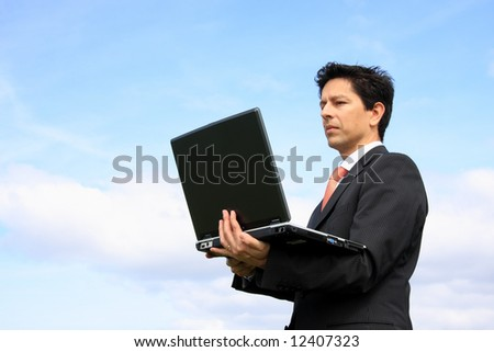 Happy business man looking to his laptop - stock photo