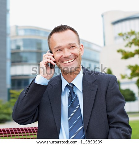 Happy business man making a call with his smartphone outside - stock photo