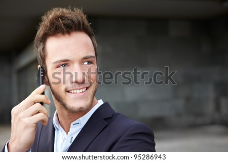 Happy business man making calls with smartphone in city - stock photo