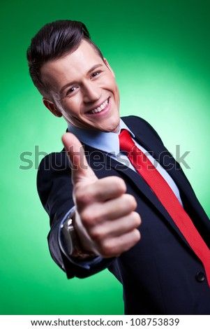 Happy business man on green background holding thumbs up ok sign - stock photo