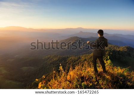 Happy business man on mountain  and sunset  - stock photo