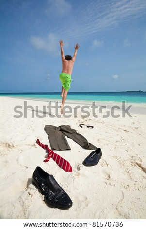 Happy business man running in to ocean to swim with clothes such as boots, tie and pants taken off and laying on the white sand - stock photo