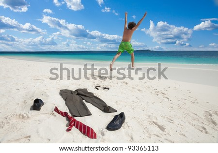 Happy business man running in to ocean to swim with clothes such as boots, tie and pants taken off and left on the white sand - stock photo
