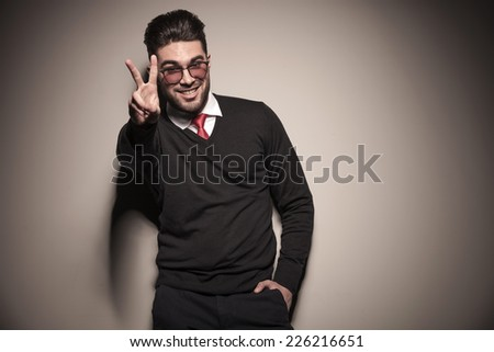 Happy business man showing the victory sign while holding one hand in his pocket.