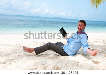 Happy business man sitting and working on the beach with tablet computer - stock photo