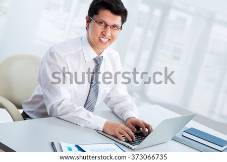 Happy business man sitting in front of laptop