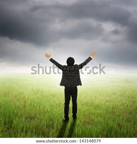 Happy Business Man standing to rainclouds in grassland - stock photo