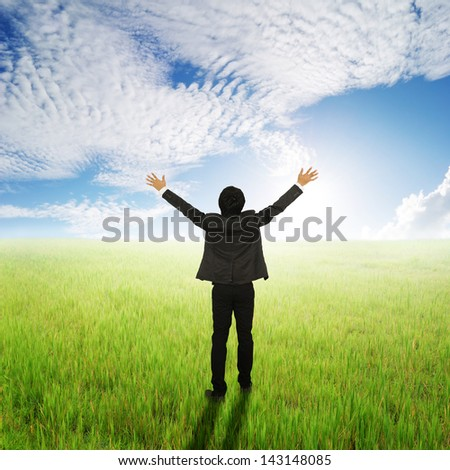 Happy Business Man standing to sun sky in grassland - stock photo