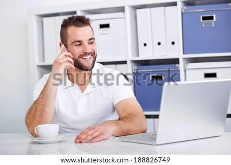 Happy business man talking on the phone in office - stock photo