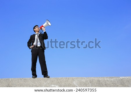 happy business man using megaphone shouting with blue sky background, asian