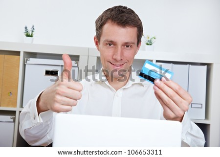 Happy business man with credit card holding thumbs up in the office - stock photo