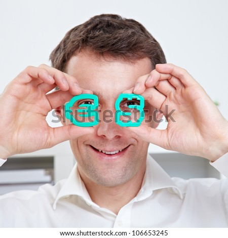 Happy business man with Euro and Dollar signs in front of his eyes - stock photo