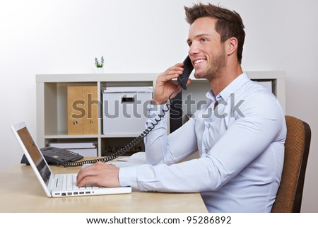 Happy business man with laptop computer in office making phone calls - stock photo